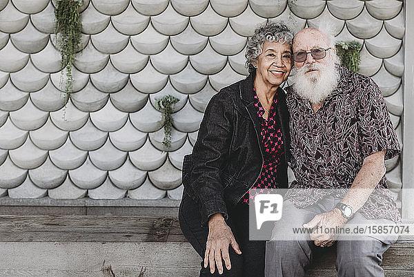 Porträt eines aktiven älteren Paares  das draußen sitzt und lächelt