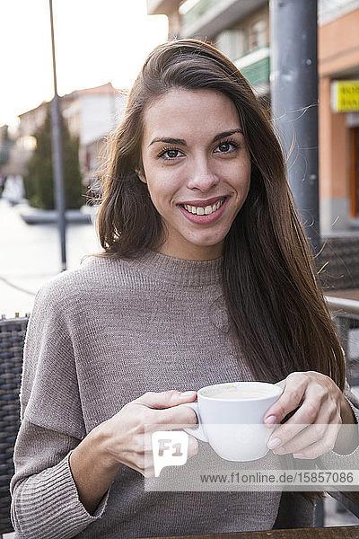 Porträt einer lachenden Frau  die eine Tasse Kaffee hält