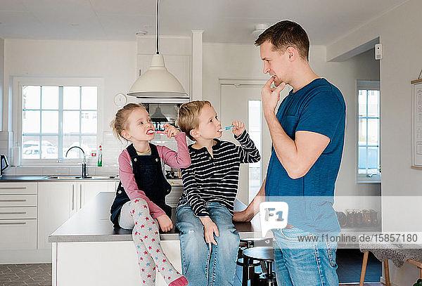 Vater  der seinen Kindern zeigt  wie sie sich vor der Schule die Zähne putzen