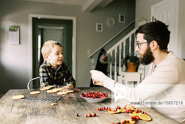 Father and son making orange and cranberry garlands for Christmas.