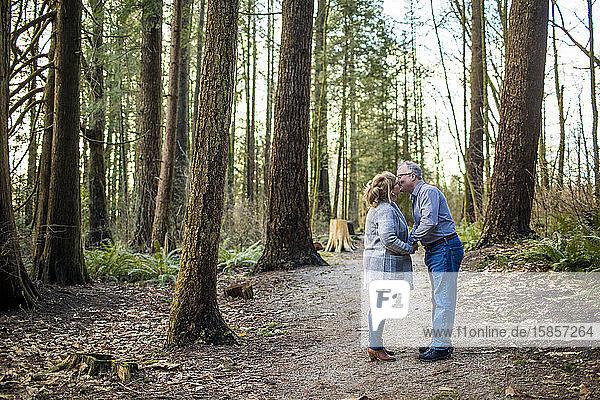 Ehepaar im Ruhestand küsst sich im Wald.
