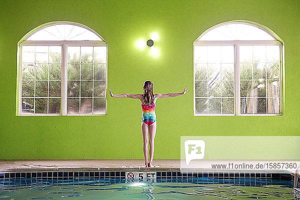 Junges Mädchen steht am Rand einer Schwimmhalle und streckt die Arme aus