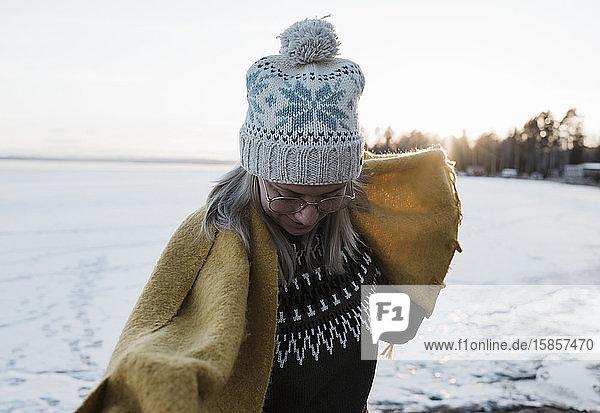 Porträt einer Frau  die einen Schal hält  während sie auf einem gefrorenen See spazieren geht