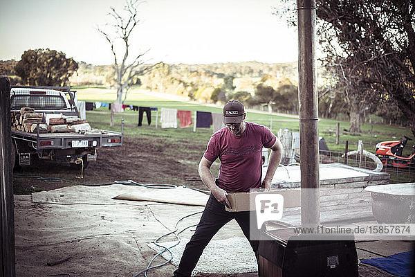 junger männlicher Bauer mit Mütze arbeitet im australischen Farmschuppen