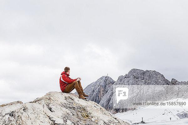 junger tausendjähriger Mann geniesst die Aussicht auf die Alpen auf einem Gletscher