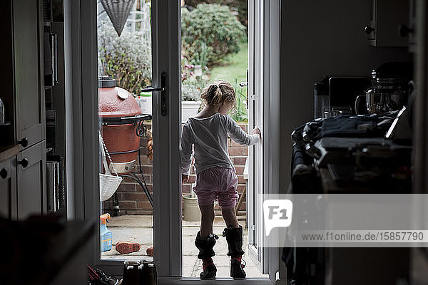 young girl standing in a doorway whilst it rains outside in summer