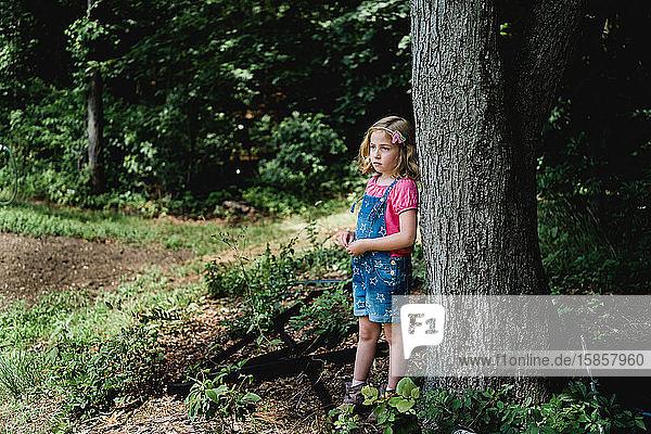 Ein kleines Mädchen steht neben einem Baum auf einem Bauernhof.