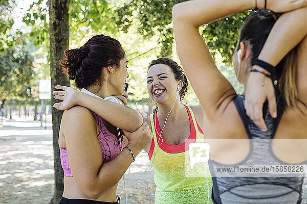 Junge Freundinnen lachen beim Aufwärmtraining im Park