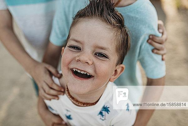 Nahaufnahme eines jungen 2-Jährigen  der in die Kamera lächelt  während die Brüder ihn umarmen