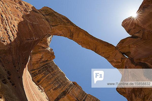 Sandstone rock arch with sunburst against blue sky in Colorado