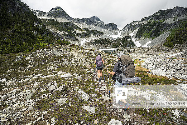 A couple hikes along a trail for a night of camping in the mountains.