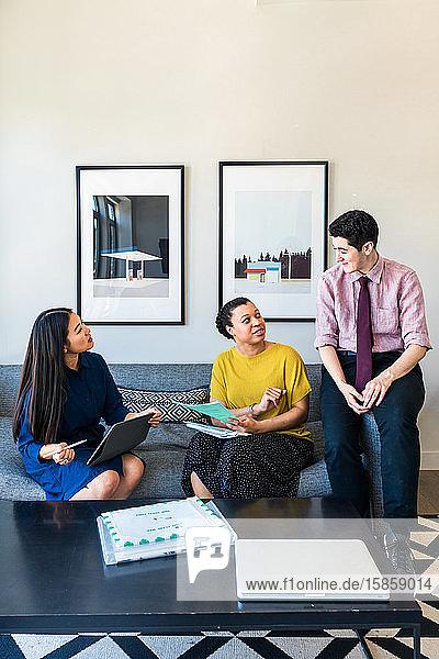 Männliche und weibliche Geschäftskollegen planen Strategie  während sie im Büro auf dem Sofa sitzen