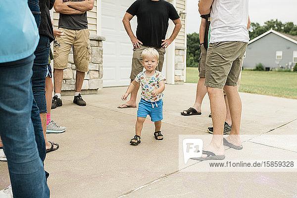 Kleinkind mit unordentlichem Gesicht rennt durch Erwachsenenbeine im Außenhaus