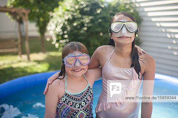 Mädchen zwischen 10 und 12 Jahren tragen eine Schwimmbrille und legen ihre Arme umeinander