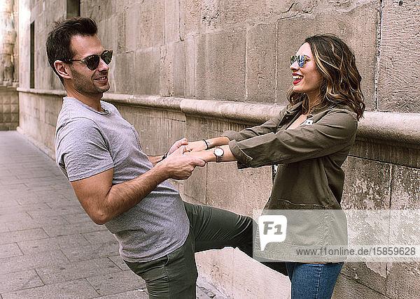 Ein junges und attraktives Paar  das sich an den Händen hält  spielt und zeigt seine