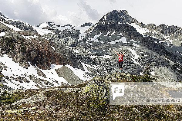Eine Frau steht auf einem Felsen und feiert Kanada an einem Sommertag in den Bergen von Britisch-Kolumbien.