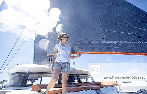 A woman onboard a catamaran enjoying a beautiful sunny day during a cr