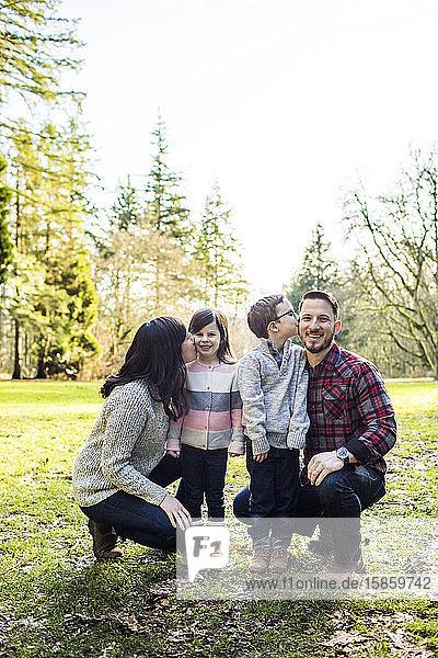 Liebevolle vierköpfige Familie  die im Freien posiert.