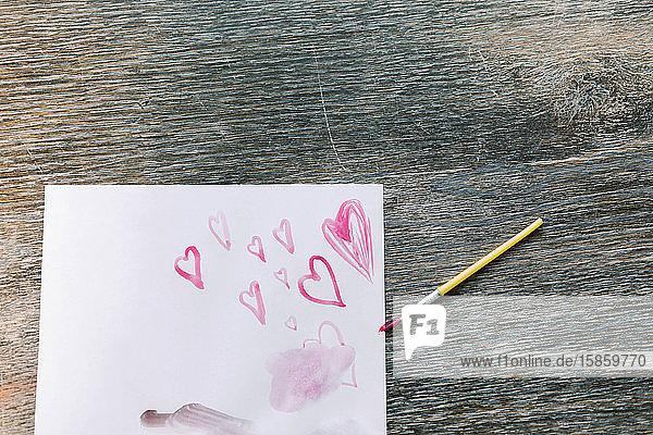 Kleines Mädchen  das mit seiner Mutter einen Ball malt.