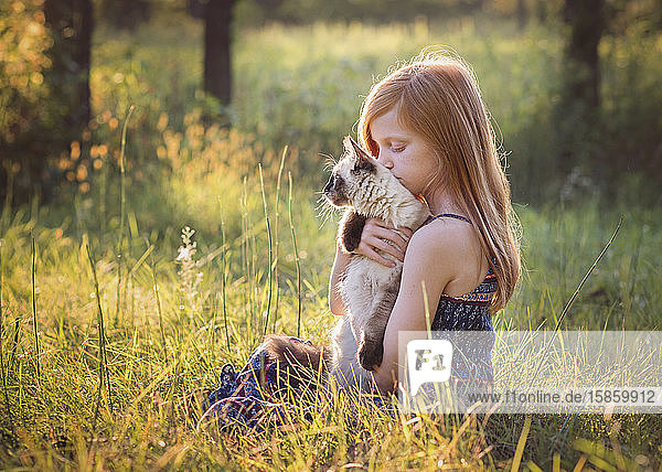 Young Girl With Kitten Outside in Meadow