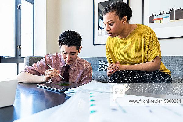Kollegin betrachtet Geschäftsmann mit Grafiktablett  während sie im Büro sitzt