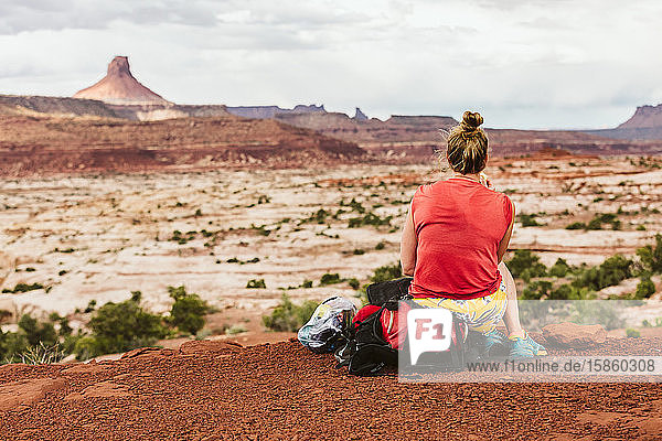 sweaty female sits on backpack during a hiking break at desert view