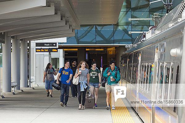 Reisende steigen am Bahnhof Denver International Airport in den Zug