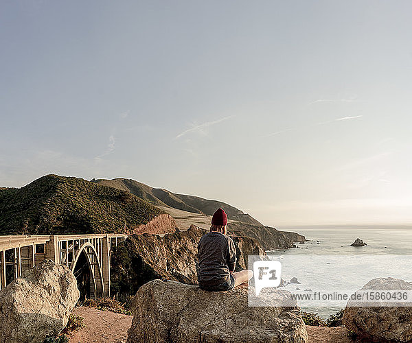 Frau sitzt auf einem Felsen mit Blick auf die Küste von Big Sur und Bixby Br