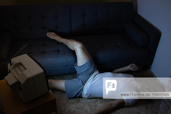 A man falls to the floor from the couch while watching an old television