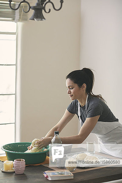 Frau in Schürze knetet zu Hause Teig auf dem Tisch an der Wand