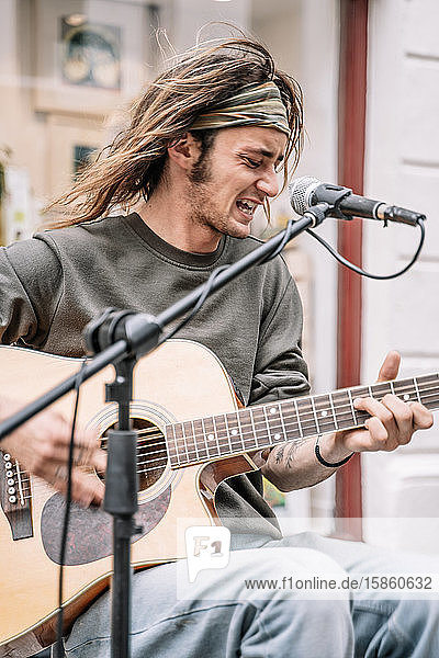 Young rocker with long hair and a headband playing guitar in front of a microphone