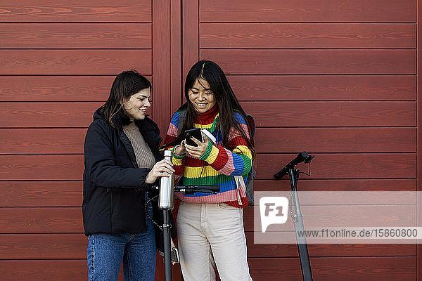 Asiatin zeigt Freundin Mobiltelefon  die am E-Roller steht