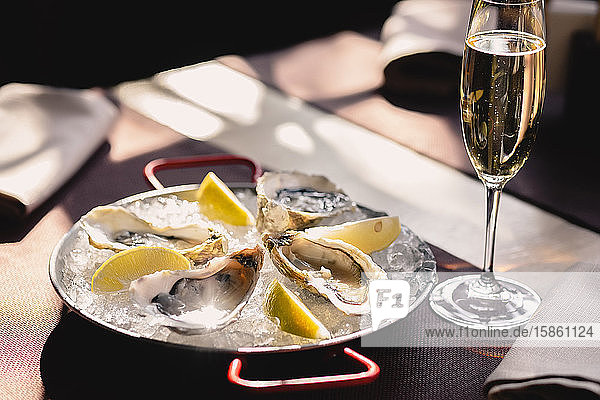 Plate with oysters  lemon and ice and a glass of champagne