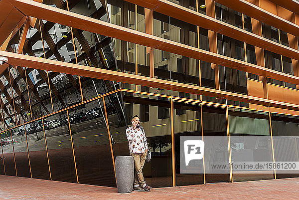 Casual wear man standing against office building while using mobile