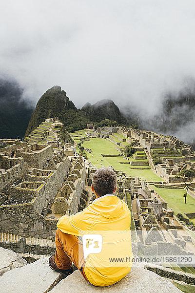 A man in a yellow jacket is sitting near ruins of Machu Picchu  Peru