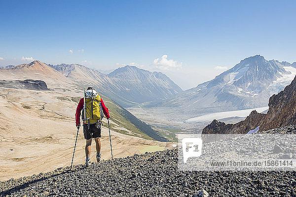 Rückansicht eines männlichen Rucksacktouristen im Hochgebirge.