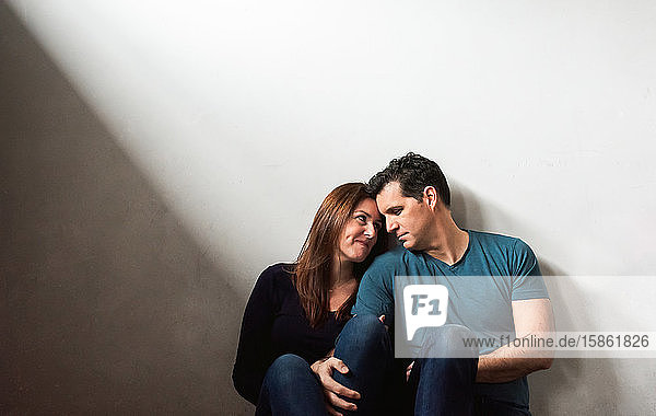 Ein Paar  das zusammen an einer weißen Wand sitzt und sich gegenseitig anschaut.