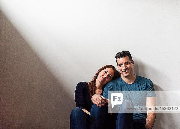 Ausgeschnittenes Bild eines Paares  das zusammen an einer weißen Wand sitzt.