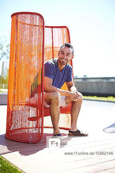 Ein Mann  der draußen in einem farbenfrohen modernen Stuhl sitzt.
