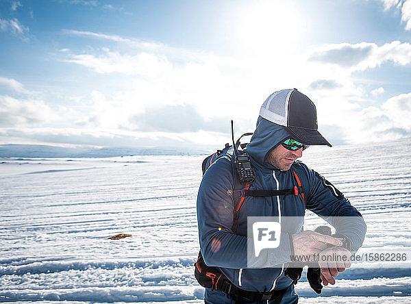Mann mit Funkgerät überprüft seine GPS-Uhr im Schnee