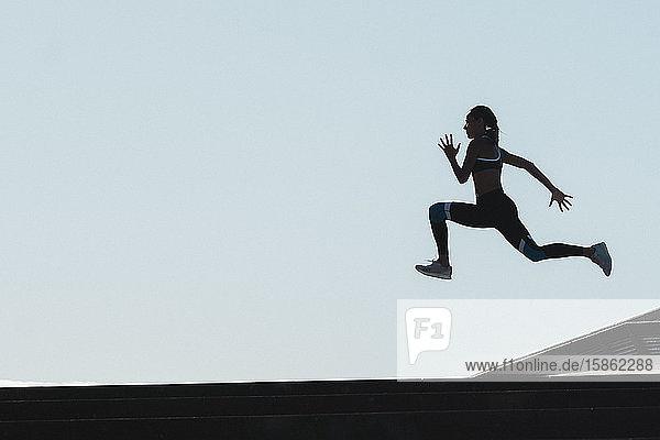 Silhouette einer Athletin  die gegen den blauen Himmel springt