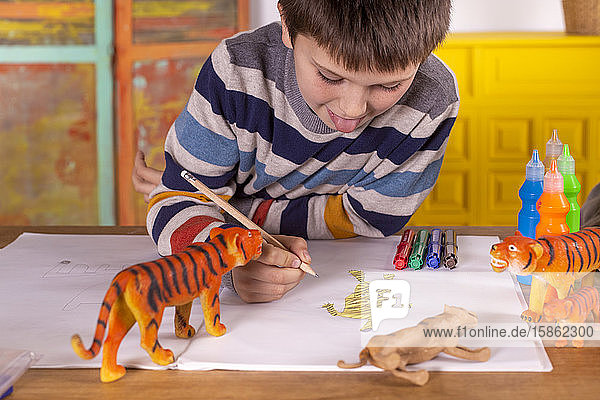 Boy sitting at a table drawing a tiger.