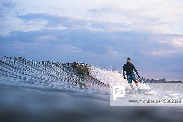Surfen im mittleren Alter bei Sonnenuntergang