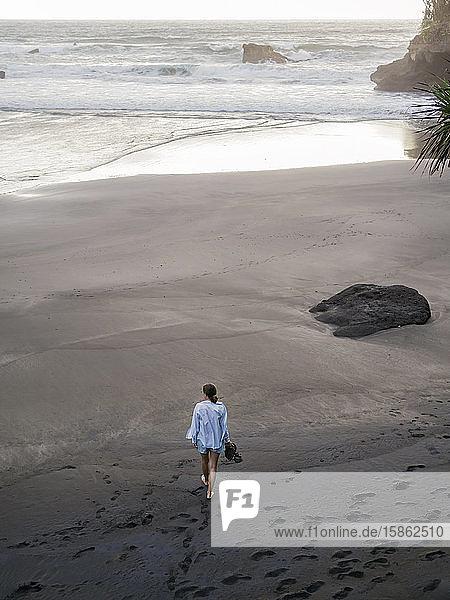 Junge Frau  die an einem felsigen Strand spazieren geht und die Aussicht betrachtet