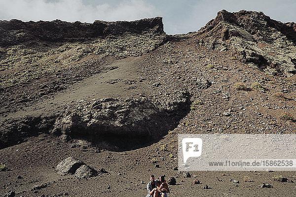 Ehepaar sitzt im Inneren des Vulkans Cuervo auf Lanzarote  Timanfaya.