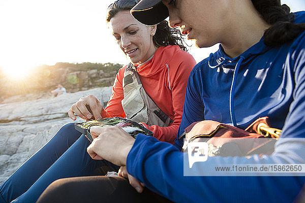 Zwei Frauen betrachten ihre Fliegenauswahl beim Fliegenfischen vor der Küste von Maine.