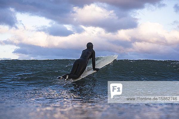 Frau surft am Wintertag bei Sonnenuntergang