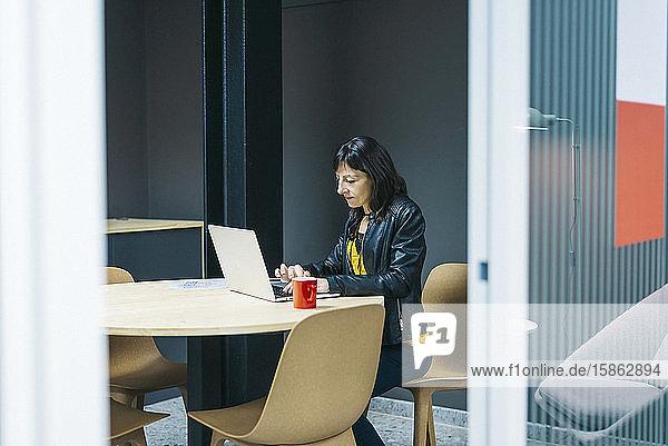 Unternehmer  der im Büro mit einem Laptop arbeitet