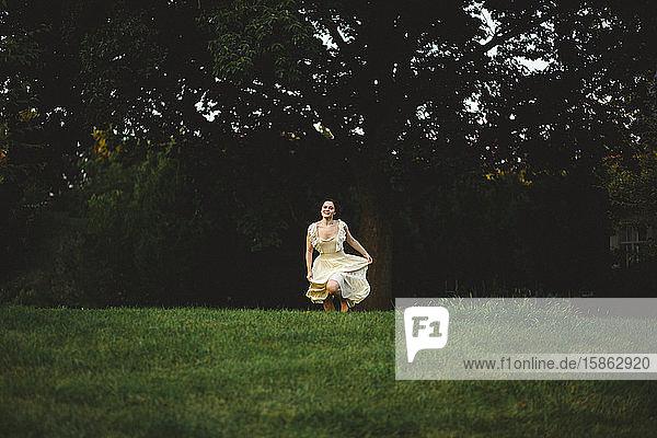 Eine junge Frau in einem fließenden Kleid läuft über ein dunkles  von Wald bedecktes Feld