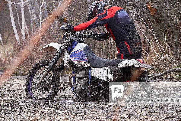 Mann fährt Motorrad im Dreck